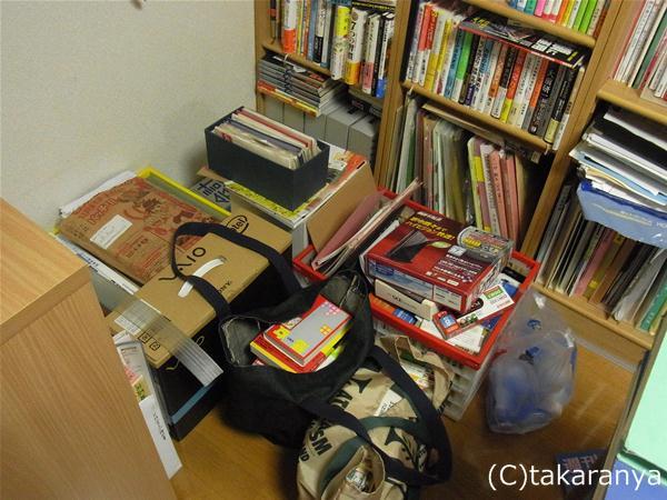 本棚前にものが積み上がって残念な感じ